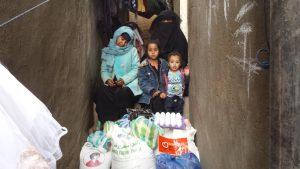 mujeres y niños recibiendo alimentos en Yemen